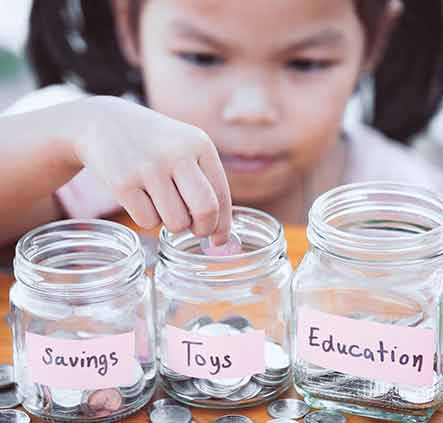 Young girl putting money in savings jars.